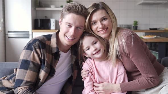 Glückliche Eltern umarmt niedliche kleine Tochter, die zu Hause auf der Couch sitzt