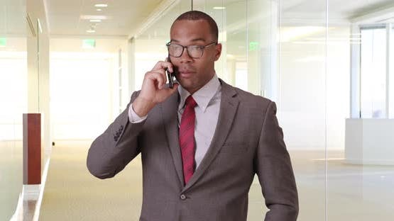 A black man uses his mobile phone for business