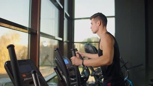 Mann auf elliptischen Fitnessgeräten.