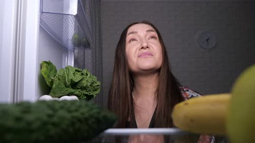 Thoughtful Woman Looks for Snacks and Chooses Green Apple