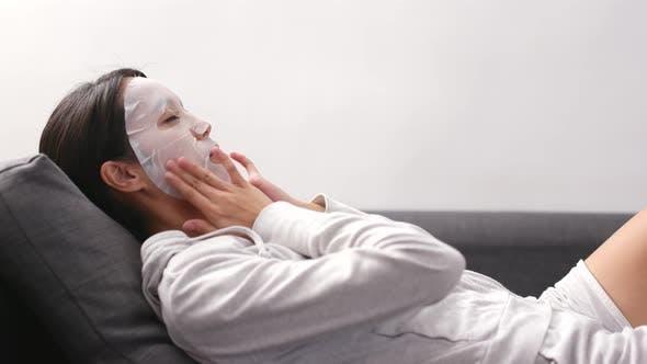 Thumbnail for Woman applying facial mask and lying on sofa