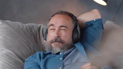 Caucasian Senior Listening to Podcast on Sofa
