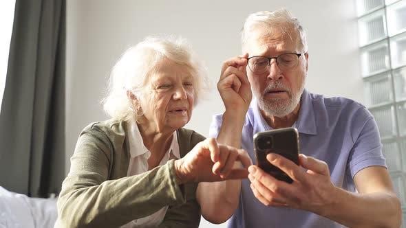 Ein älteres Ehepaar sitzt zu Hause auf einem Bett und versteht zusammen moderne Technologien das Internet In