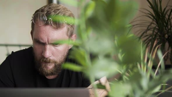 Bearded Man at Computer at Home