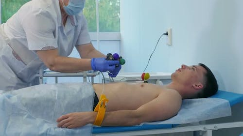 Nurse Attaching ECG Electrode Pads To Male Patient's Chest