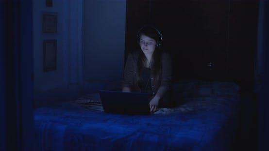 Женщина наслаждается музыкальным видео ночью