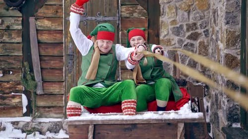 Christmas elves ride wooden sledges. New Year is coming. Christmas eve.