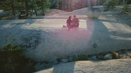 Thumbnail for Drone Flying Away From Happy Romantic Couple Sitting and Talking Together on a Rock