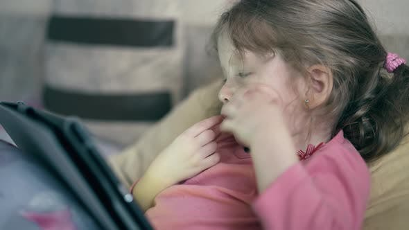 CU: Portrait of Pretty Little Girl, Child Who Lies on the Sofa Under Blanket and Plays on a Tablet