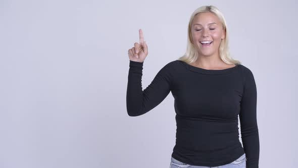 Thumbnail for Young Happy Blonde Woman Thinking and Pointing Up