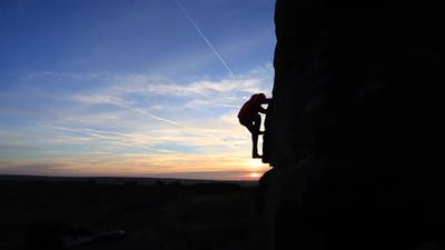 Silhouette of a man climbing boulders while bouldering.