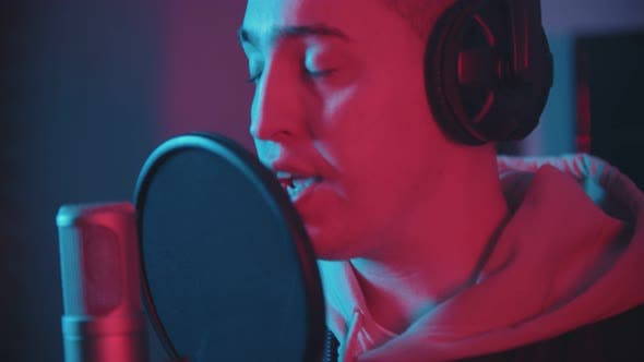 Thumbnail for A Man in Headphones Rapping Through the Pop-filter in the Microphone