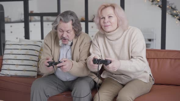 Thumbnail for Cheerful Absorbed Senior Man and Woman Playing Video Games with Game Consoles. Portrait of Joyful