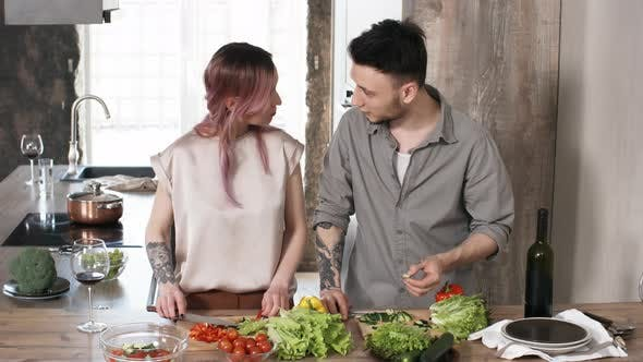 Cover Image for Young Happy Couple Cooking Dinner Together and Trying Vegetables