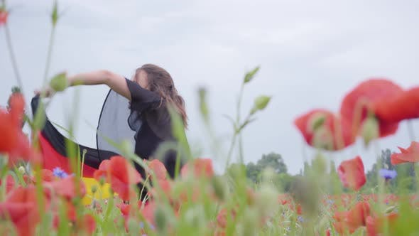 Thumbnail for Cute Adorable Young Girl Dancing in a Poppy Field Holding Flag of Germany in Hands Outdoors