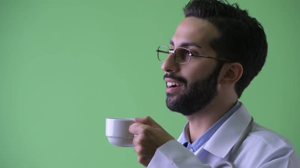 Cover Image for Closeup Profile View of Happy Young Bearded Persian Man Doctor Drinking Coffee