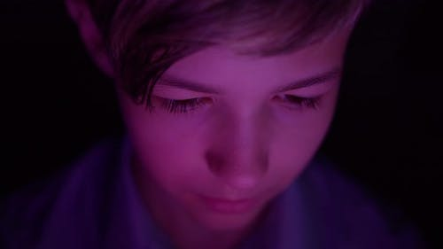 Portrait of a Boy Playing a Computer Game on the Tablet at Night