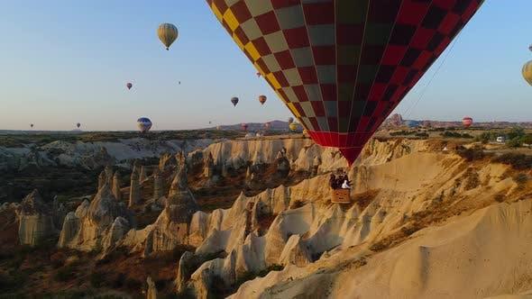 Tourist And Balloons In Cappadocia