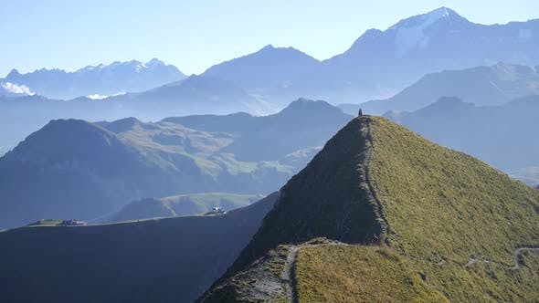 A man mountain biking across a European mountain range.