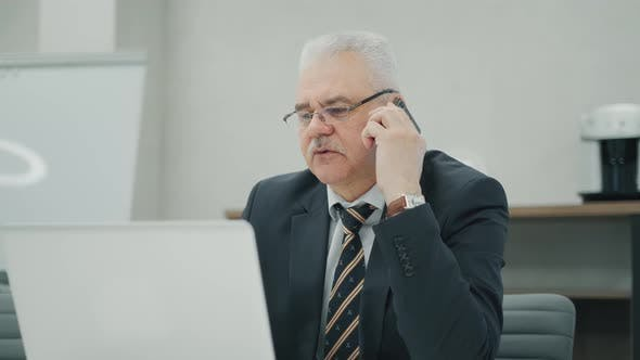 Handsome Old Businessman in Formal Clothes and Eyeglasses Is Talking on the Mobile Phone, Using a
