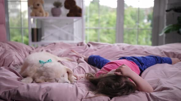 Thumbnail for Sweet Little Girl Cuddling Sleepy Puppy in Bed