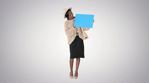 African American Woman Holding a Blank Placard on Gradient Background