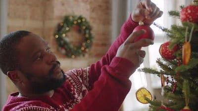 Cheerful Black Man Decorating Christmas Tree at Home