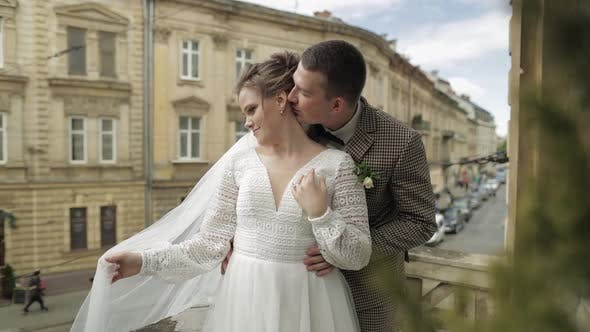 Newlyweds. Caucasian Groom with Bride Kissing on Balcony. Wedding Couple. Man and Woman in Love