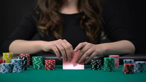 Woman Checking Cards and Betting Casino Chips
