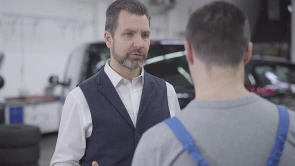Thumbnail for Close-up Portrait of Displeased Caucasian Man Talking with Unrecognizable Auto Mechanic. Adult