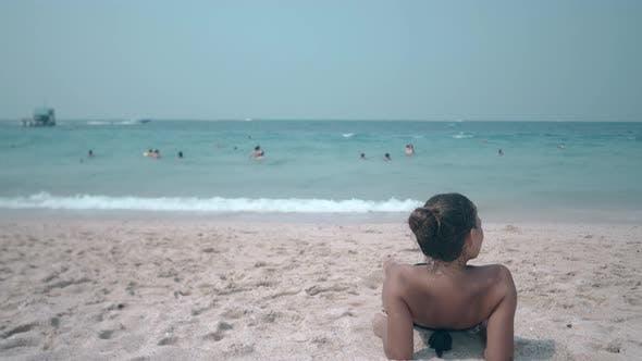 Thumbnail for Brunette in Black Bikini with Open Shoulders Lies on Beach