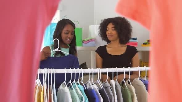 African American friends shopping and trying on clothes