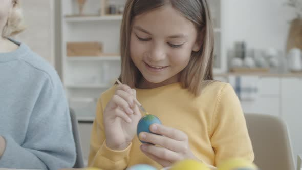 Girl and Grandmother Decorating Easter Eggs