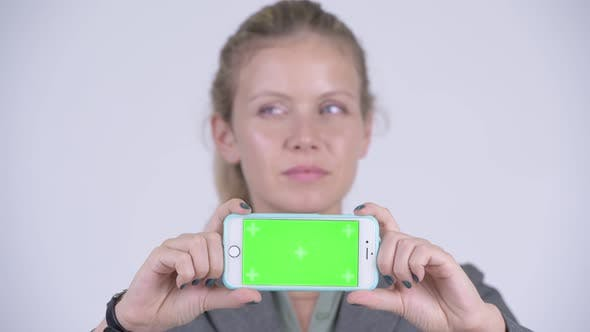 Cover Image for Face of Young Happy Blonde Businesswoman Thinking While Showing Phone