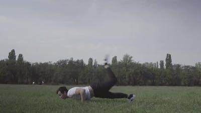 Wide Shot of Young Break Dancer Dancing on Green Summer Meadow
