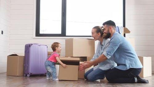 Das kleine Kind hält eine kleine Kiste. Eltern warten auf ein Kind mit einer Box.