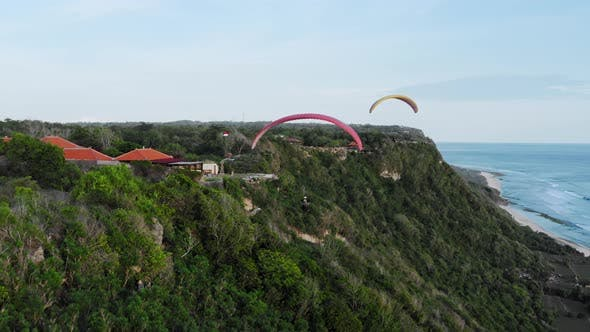 Aerial Drone Flight Over The South Coast At Sunset, Bali, Indonesia, Two Paragliders Flying To Each