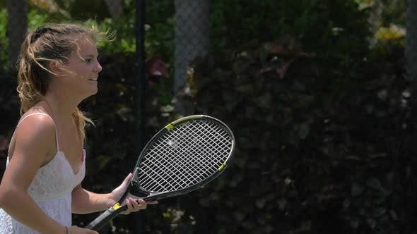 Thumbnail for A young woman playing tennis with her boyfriend while on vacation.