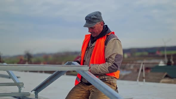 Thumbnail for Worker attaches metal basis for solar panels