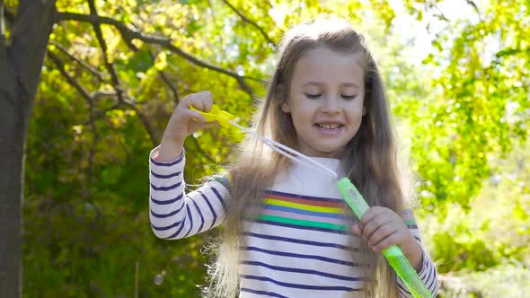 Thumbnail for Pretty Brunette Girl Staying in Autumn Sunrays and Blowing Soap Bubbles. Little Child in Striped