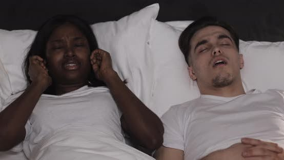 Thumbnail for Multi-ethnic Couple Lying in Bed Together. Woman Suffers From Her Partner Snoring in Bed