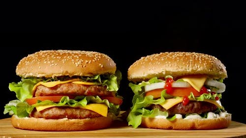 Two Craft Beef Burgers on Wooden Table Isolated on Dark Grayscale Background