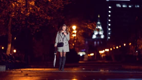 The Girl Walks with an Umbrella in the Night City