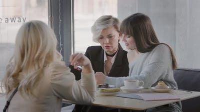 Four Female Friends in a Modern Cafe