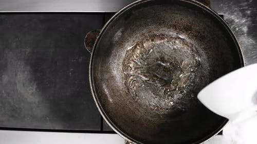 Pouring Oil into Cast Iron Skillet
