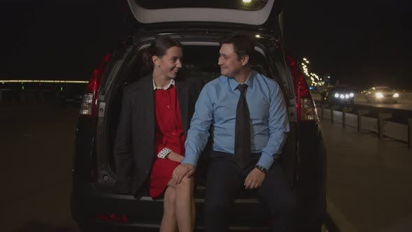 Man Flirting with Businesswoman in Car at Night