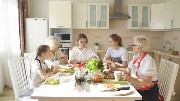Portrait of Young Generation with Grandmothers Talking Over Cup of Tea at Home
