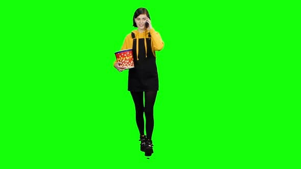 Thumbnail for Teenager Speaks on the Phone with Popcorn in His Hands. Green Screen