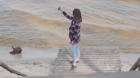 Thumbnail for Wide Shot of Attractive Caucasian Girl Taking Selfie Standing on Pier. Brunette Young Woman Posing