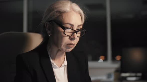 Cover Image for Grey-Haired Female Employee Working in Office Late at Night